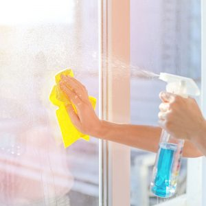Person Spraying Cleaner on Window While Wiping