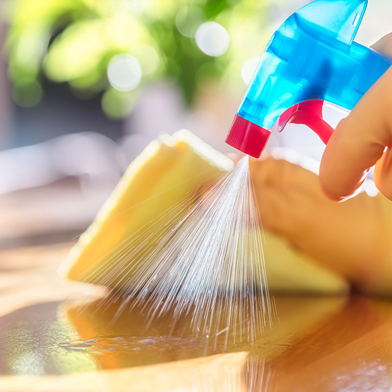 Person Spraying Clean on Table While Wiping Up