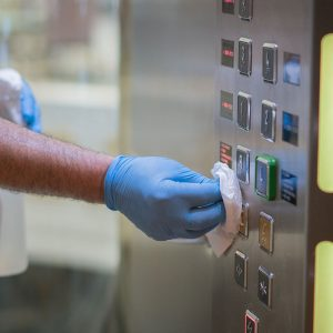 Person Wiping Elevator Buttons With Cleaner